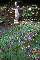Lavender herbs English and Spanish types planted with flowers and climbing vines Clematis on wicker privacy fence, with Grecian statue of a woman holding an urn.