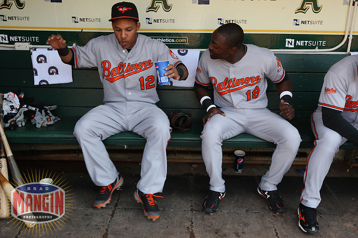 OAKLAND, CA - JUNE 6:  Robert Andino #12 (left) dances as Felix Pie #18 of the Baltimore Orioles watches in the dugout before the game against the Oakland Athletics at the Oakland-Alameda County Coliseum on June 6, 2009 in Oakland, California. Photo by Brad Mangin