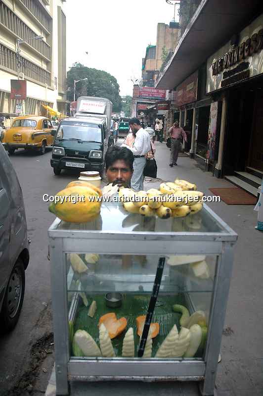 A man selling fruits on a foot path at New-market area of Kolkata. Street food stalls are serving the office goers for decades. All kind of Indian foods are available on the street at an affordable price. They sale them openly. Street food stalls are another results of unempoloyment and over poppulation. They serve millions of people in India. Kolkata, West Bengal,  India  7/18/2007.  Arindam Mukherjee/Landov