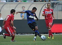 Manchester United midfielder Nani (17) shows off his skill with behind-the-leg pass in between Chicago Fire defender Gonzalo Segares (13) and midfielder Bratislav Ristic (77).  Manchester United defeated the Chicago Fire 3-1 at Soldier Field in Chicago, IL on July 23, 2011.