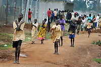 Children leave Noah's Ark Childrens Ministries Child Shelter for Moral and Peace  Building in Gulu, January 25, 2004. The center hosts about 2,000 children nightly who stay in the safety of the city limits to avoid abduction by the Lord's Resistance Army. Others stay because the LRA violence has chased their families into smaller accomodations near the city, leaving the family witout enough sleeping space for the whole family. (Rick D'Elia)