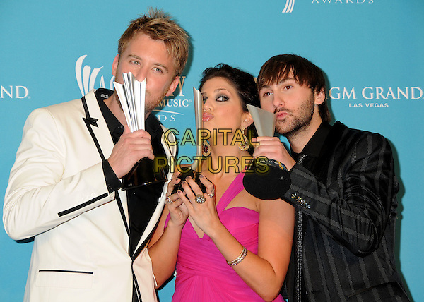 Charles Kelley, Hillary Scott and Dave Haywood of Lady Antebellum.45th Annual Academy Of Country Music Awards - Press Room held at the MGM Grand Garden Arena, Las Vegas, Nevada, USA..April 18th, 2010.ACM half length white cream suit jacket award trophy beard facial hair black pink one shoulder dress trophies kiss kissing .CAP/ADM/BP.©Byron Purvis/AdMedia/Capital Pictures.