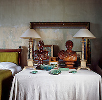 A detail of a traditional bedroom. The stone walls are painted with natural pigments inspired by the colours of Provence, while being careful to leave the original underlying layers. Two lamps, wooden busts, several pottery pieces and an empty picture frame are arranged on a table covered with a white cloth.