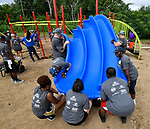 Volunteers position a triple slide as they assemble the playground equipment. Volunteers from the Pacific Life Foundation, Edward Jones, the Riverview Gardens School District, the Boys & Girls Clubs of Greater St. Louis and the community joined KaBOOM! and transformed an empty site into a kid-designed, state-of-the-art playground at Highland Elementary School on Saturday August 18, 2018. The playground - designed from students' drawings - will give more than 400 kids a safe place to play. KaBOOM! is a national non-profit dedicated to bringing balanced and active play into the daily lives of all kids.  Photo by Tim Vizer