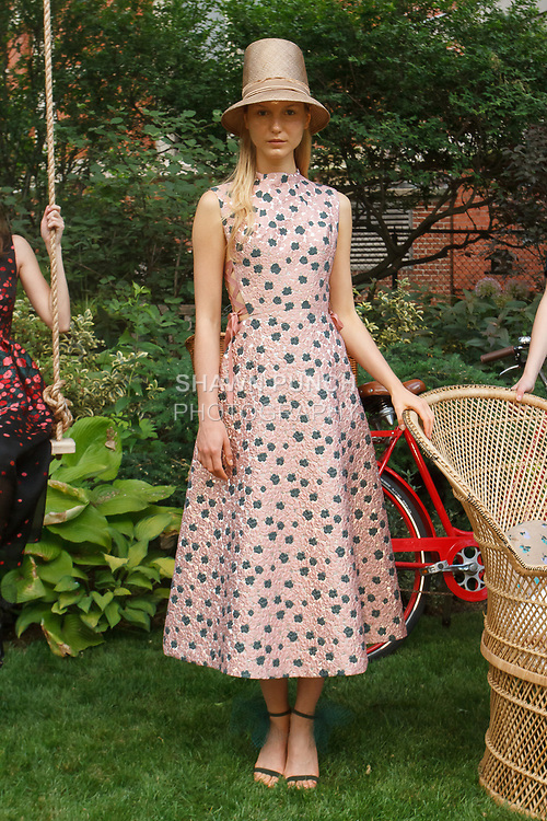 """Model poses in a dusty pink and moss mirror brocade dress with laced brosgrain at side, from the Lela Rose Resort 2018 """"Garden Party"""" collection in Jefferson Market Garden on June 7 2017, during Resort Fashion Week in New York City."""