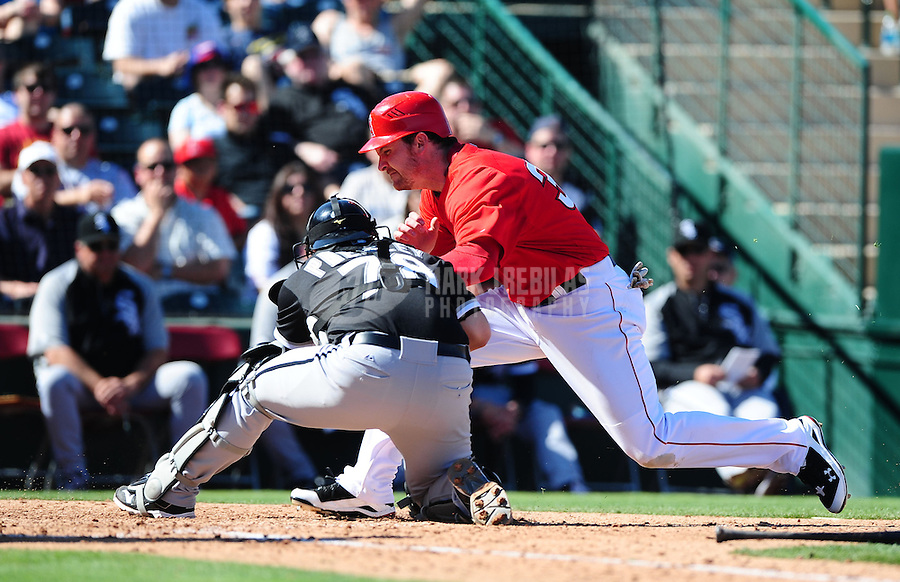 Mar. 6, 2012; Tempe, AZ, USA; Chicago White Sox catcher Josh Phegley tags out Los Angeles Angels base runner Ryan Langerhans in the third inning during a spring training game at Tempe Diablo Stadium.  Mandatory Credit: Mark J. Rebilas-