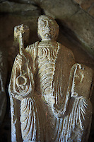 """Early Anglo Saxon sulpture of the St Peter now part of the south porch of Malmesbury Abbey, Wiltshire, England. The apostles, apart from Peter who holds a crude key, have no distinguishing feature to allow identification. Some are holding books, none have halos and some hold their heads at awkward angles and the statue of Peter has no beard. These  styles are typical of Anglo Saxon art. The two panels are 10 ft long and 4ft 6"""" high are date from the original Ango Saxon church of 705. They were probablbly built into the proch during the Norman rebuilding. The style of these sculptures is of the Roman Byzantine style and were probably sculpted by masions from Gaul.  Malmesbury Abbey, Wiltshire, England"""