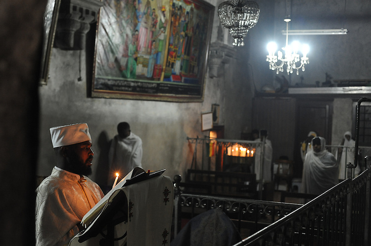 A cleric and pilgrims during prayer at the Ethiopian section of the Church of the Holy Sepulchre in Jerusalem's old city, Israel. The church sits on the site where Jesus Christ is believed to have been crucified and buried.