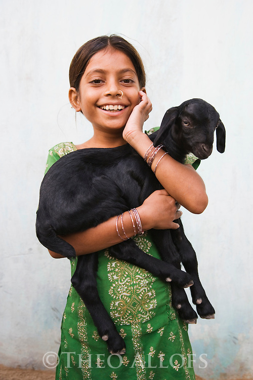 Young Gujarat girl holding her baby goat in a small village near the Little Rann of Kutch; portrait, Gujarat, India --- Model Released
