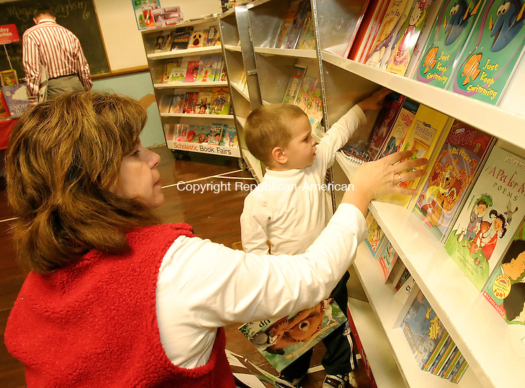 NAUGATUCK, CT 7 November 2005 -110705BZ08- David Green Jr., 3, and his mother Lisa Green, of Naugatuck, look through the books for sale during a book fair at Salem School Monday night. David's older sisters are students at the school.<br /> Jamison C. Bazinet Republican-American