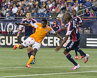 Houston Dynamo midfielder Warren Creavalle (5) kicks for goal as New England Revolution defender Jose Goncalves (23) leaps to intercept the ball.  The New England Revolution played to a 1-1 draw against the Houston Dynamo during a Major League Soccer (MLS) match at Gillette Stadium in Foxborough, MA on September 28, 2013.