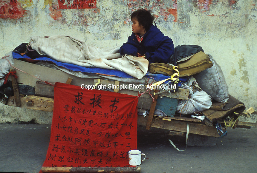 A baby girl beggar sits upon a cart in Guangzhou begging for money, the sign says that she is also for sale. An average gender inbalance 118 males to 100 females caused by the strict One Child Policy and the preference for boys means that there is a shortage of women in China.