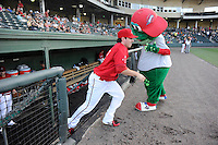 Third baseman Jimmy Rider (5) of the Greenville Drive bumps fists with mascot Reedy Rip'It as he is introduced before a game against the Lexington Legends on Sunday, August 31, 2014, at Fluor Field at the West End in Greenville, South Carolina. Greenville won, 3-2. (Tom Priddy/Four Seam Images)