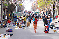 A street market in the city. People walking on the street and displaying their goods on the ground or on stalls. Montevideo, Uruguay, South America