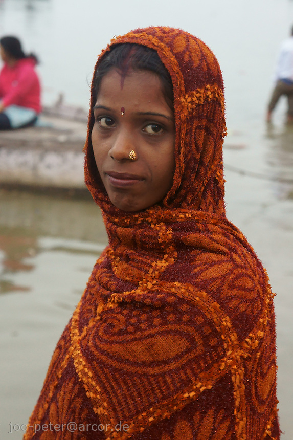 Portrait of a young mother at river Ganges during chat mata, also called Dala chhath In this ceremony women gather at the river and pray for sons and good luck of her family (a woman without a son is belived to end up in hell, also a widow is believed to be cursed and can be expelled by the family).God of the sun, Surya is asked for help in Dala chhath. Surya is one of the most acient gods in India, already known in Vedic times, where Shiva and Brahma were still unknown.