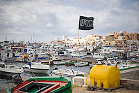 "Una bandiera a lutto con su scritto ""Vergogna"" sventola nel posto di Lampedusa dopo il tragico affondamento del barcone dove hanno trovato la morte più di 300 clandestini.<br />