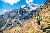 Trail running with the Weisshorn in the distance, on the descent to Randa, while on the Via Valais, a multi-day trail running tour connecting Verbier with Zermatt, Switzerland.