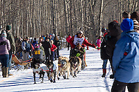 Jan Steves and team run past spectators on the bike/ski trail during the Anchorage ceremonial start during the 2014 Iditarod race.<br /> Photo by Britt Coon/IditarodPhotos.com