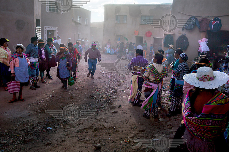 People walk down a back street in Macha during the tinku festival. <br /> <br /> The people of Macha and surrounding communities carry on the pre-Columbian tradition of ritual fighting. The communities gather on the plaza of Macha to fight and dance in competition with each other. The blood that is spilled is an offering to Mother Earth. In return, the people ask for rain and a good harvest. This ritual is called tinku or fiesta de la cruz since the cross is also engaged in the festivities. The cross is dressed up, given offerings and brought from communities around Macha to the church in town. This syncretic festival melds pagan, pre-christian rituals with Catholic practice. /Felix Features