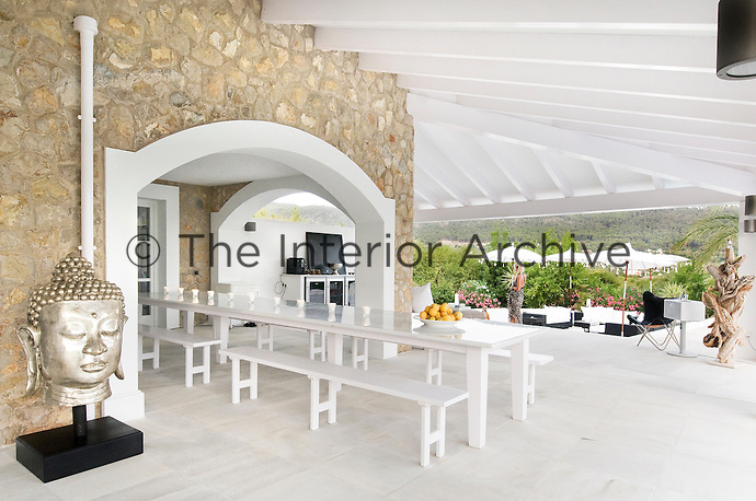 A long dining table flanked by a series of matching benches under the covered terrace is the favourite place for outdoor dining