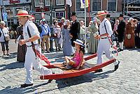 Nederland  Hoorn 2016.  Kaasmarkt in Hoorn.Kaasdragers dragen een jonge toeriste op een berrie. Foto Berlinda van Dam / Hollandse Hoogte