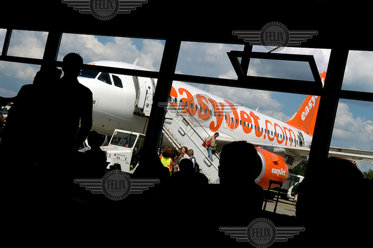 Passengers alight a low-cost airline Easyjet flight, as others in a departure lounge wait to board the aircraft at Schoenefeld airport.