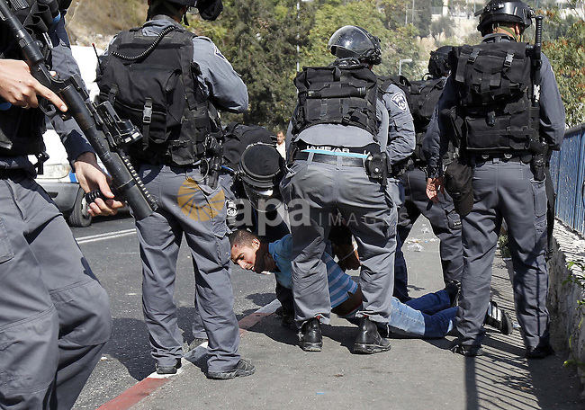 Israeli security forces arrest a Palestinian man during clashes between Palestinian protesters and Israeli police after authorities limited access for Muslim worshippers to the flashpoint al-Aqsa mosque compound on October 15, 2014 outside Jerusalem's Old City. Four Palestinians were arrested and three police were injured in the confrontation, police spokeswoman Luba Samri said. Photo by Muammar Awad
