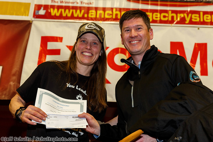 BBNC president Jason Metrokin pressents the Bristol Bay Native Corporation Fish First Award to Aliy Zirkle at the musher 's finishers banquet in Nome on Sunday March 16 after the 2014 Iditarod Sled Dog Race.<br /> <br /> PHOTO (c) BY JEFF SCHULTZ/IditarodPhotos.com -- REPRODUCTION PROHIBITED WITHOUT PERMISSION