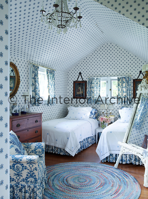 A cosy twin guest room with blue and white floral wallpaper and co-ordinating bed linen.