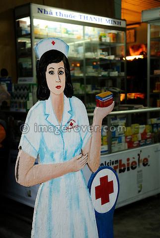 Asia, Vietnam, Hue. Figure of a nurse promoting a pharmacy.