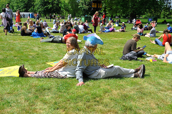 Fans<br /> attending The Big IF, Hyde Park, London, England. <br /> 8th June 2013<br /> full length costume gv general view concert goers  fish hat side profile sitting back to back<br /> CAP/MAR<br /> &copy; Martin Harris/Capital Pictures