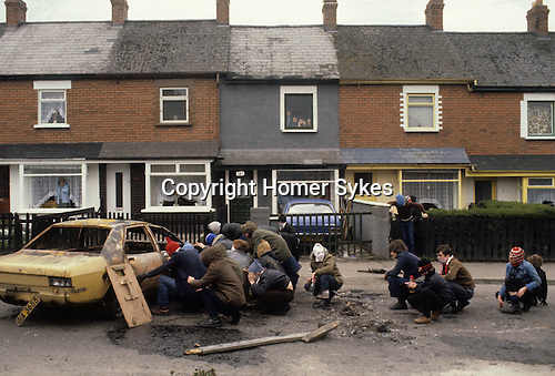Rots rioting Catholic youth attacking the British army Belfast 1981 Northern Ireland Uk 1980s Hiding behind hijacked cars.