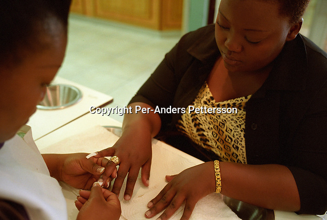 """SOWETO, SOUTH AFRICA - DECEMBER 25: (GERMANY, SOUTH AFRICA AND ITALY OUT). A middle-class black woman has a manicure at """"Romeo & Julieet"""" hair salon on December 25, 2003 at South Gate, a shopping mall, outside Soweto, South Africa. There's a slowly growing black middle-class in townships such as Soweto, and people start to own their first house, car. At South Gate, one of the busiest malls in the country, thousands of mainly black South Africans spend more money on furniture, electronic equipment and other goods. A majority of South Africans live in poverty, but for a growing number of people positive changes has happened since the fall of Apartheid and the start of democracy in the country in 1994. .(Photo: Per-Anders Pettersson/Getty Images)......"""