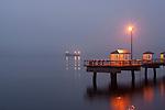 Fishing pier with tanker in Elliott Bay at sunrise in fog