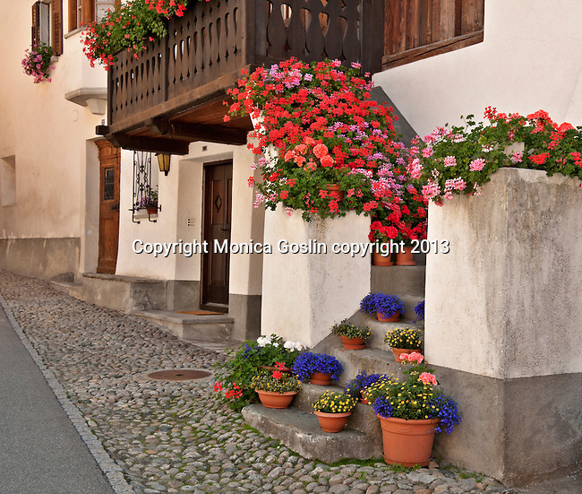 House in the small town of Viscoprano with flowers covering the stairs that lead up to the front door, in the Swiss valley of Bregaglia; the town of Viscoprano dates back to 1096