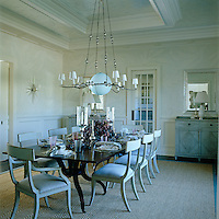 In the dining room the large table easily seats eight with chairs painted a chalky grey-blue and finished in a silver-leaf detail