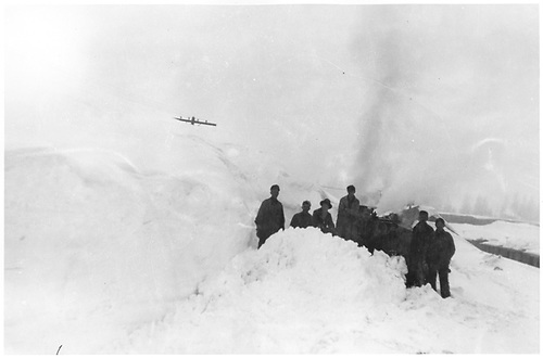 Workmen posing at large snow drift they are clearing.<br /> D&amp;RGW