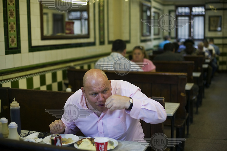 A man eats a lunch of pie, mash and jellied eels in Manze's Eel, Pie and Mash shop on Tower Bridge Road in London. This pie shop was opened in 1897 and is the oldest pie and eel shop in the country.