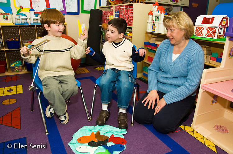 MR / Albany, New York. Clover Patch Early Childhood Day Care classroom. Clover Patch is an inclusion early childhood education program with disabled and non-disabled students at Center for Disability Services, an ungraded private school that serves individuals with disablilities. Teacher and students in inclusion classroom play fishing game with magnets to pick up and identify sight words. Left: boy, 4; center: boy, 5, Cuban-American / Caucasian, Cerebral Palsy, Spastic Diplegia, mainstreamed in inclusion classroom. MR: One1, Cal8, Haz1. ID: AH-gPcp. ©Ellen B. Senisi.