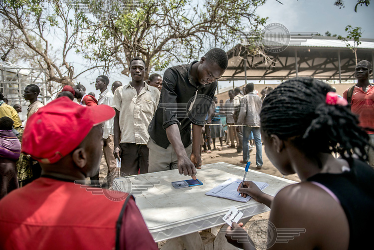 A refugee from South Sudan registers with a thumb print with Red Cross volunteers at Imvepi reception centre before collecting blankets, and other non-food items.