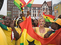 Germany, DEU, Dortmund, 2006-Jun-27: FIFA football world cup (USA: soccer world cup) 2006 in Germany; black and white Ghanaian football fans singing at a public viewing zone on the Friedensplatz before the world cup match Brazil vs. Ghana (3:0).