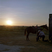 Cowboy Church. Texas, USA. 2007. A parishioner of the church prepares his horse at sunset just before roping night at the cowboy church.