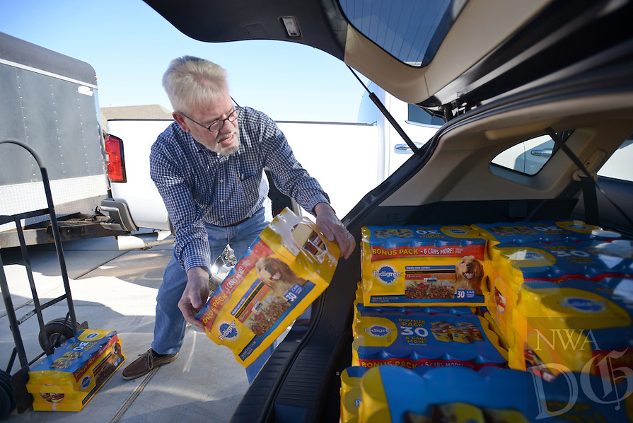 NWA Democrat-Gazette/BEN GOFF @NWABENGOFF<br /> Randy Imbeau of Springdale loads dog food into a vehicle on Sunday Dec. 6, 2015 as volunteers with the Chase Family Foundation distribute food for home-bound seniors and their pets. The organization's annual holiday distribution seeks to provide enough food for seniors and their pets to get through the holidays and periods of inclement whether when Meals on Wheels doesn't operate.