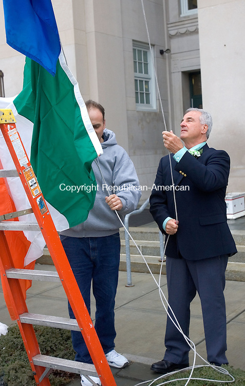 TORRINGTON CT. 17 March 2015-031715SV06-Francis L. DuCotey ,&quot;Lord Mayor&quot;, raises the flag of Ireland during the Saint Patrick's Day celebration at City Hall in Torrington Tuesday.<br /> Steven Valenti Republican-American