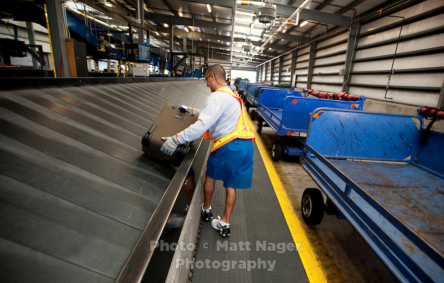 "Southwest Airlines employee Percy Mota (cq) moved bags at Southwest Airlines facilities at Love Field Airport in Dallas, Texas, Wednesday, October 27, 2010. A big selling point for Southwest Airlines has been their ""Bags Fly Free"" campaign...PHOTO/ MATT NAGER"