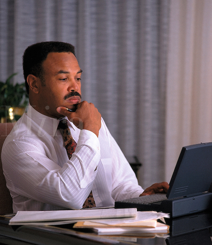 African-American man in hotel room pondering figures on laptop computer; professional; concentration; dedication; calculating; computers, travel, Black businessman 4x5 orig. Dave Johnson.