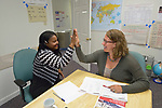 Mimose Jeanbaptiste (left), a Haitian refugee, gets a high five from Cas Cogswell, a paralegal with Church World Service, as she finishes practice for a U.S. citizenship examination in Durham, North Carolina. <br /> <br /> Church World Service assists refugees with resettlement and other services in North Carolina and throughout the United States.<br /> <br /> <br /> Photo by Paul Jeffrey for Church World Service.