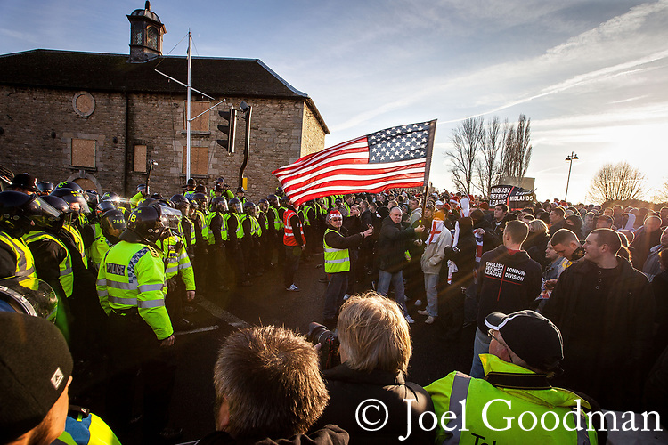 © Joel Goodman - 07973 332324 . 11/12/2010 . Peterborough , UK . An EDL supporter waves an American flag at the demonstration . The English Defence League ( EDL ) hold a demonstration in Peterborough . Photo credit : Joel Goodman