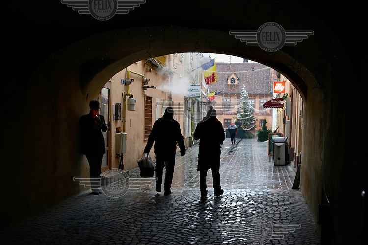 A restaurant employee (at left) lights up her cigarette during a break from work as people pass through one of the ornate archways in the medieval town centre.