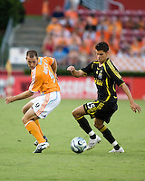 Columbus Crew forward Ricardo Virtuoso (25) dribbles around Houston Dynamo midfielder Brian Mullan (9). The Houston Dynamo tied the Columbus Crew 1-1 in a regular season MLS match at Robertson Stadium in Houston, TX on August 25, 2007.
